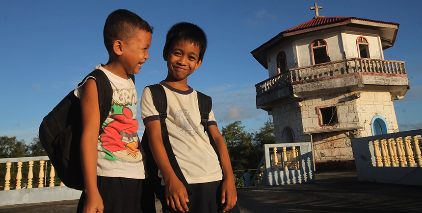 Kids walk by Cuyo Fort on their way to school